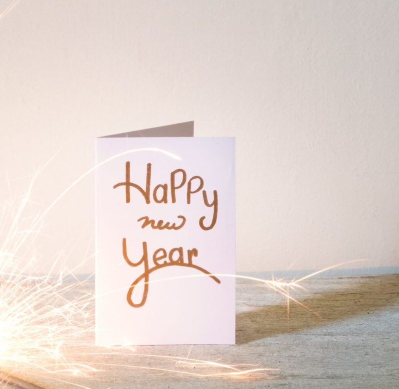 new-year-card-with-lit-sparkler-on-table-against-wall-688969401-5bd668bc46e0fb0026718605 (2)